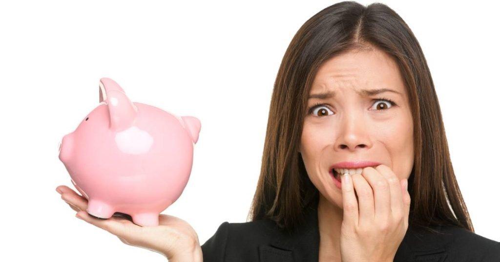 woman holding piggy bank: money worries